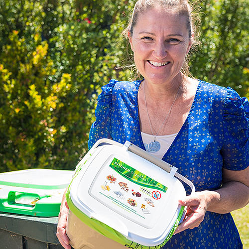 Bega Valley Waste Management Coordinator Joley Vidau with new kitchen caddies that the council will deliver to residents when it introduces FOGO.