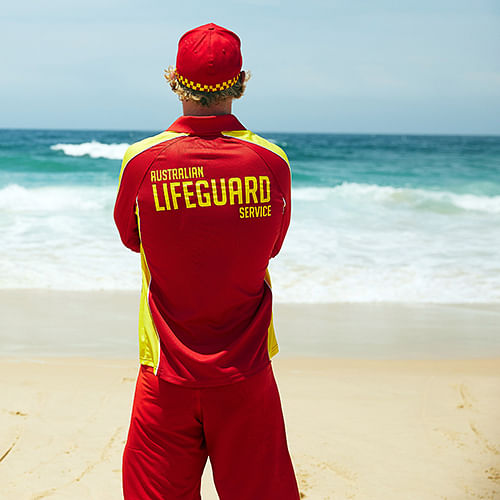 member of the Australian Lifeguard Service looks out to the beach surf