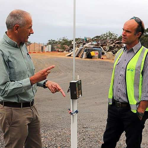Euan Ferguson (Tathra and District bushfire Recovery Coordinator at the time) and Toby Browne (Council's Waste and Recycling Manager during the clean-up) inspect an air monitoring device installed at the Eden Waste Depot to ensure the safety of the public.