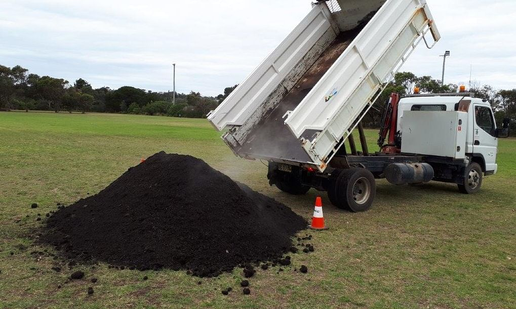 Waste truck emptying compost.