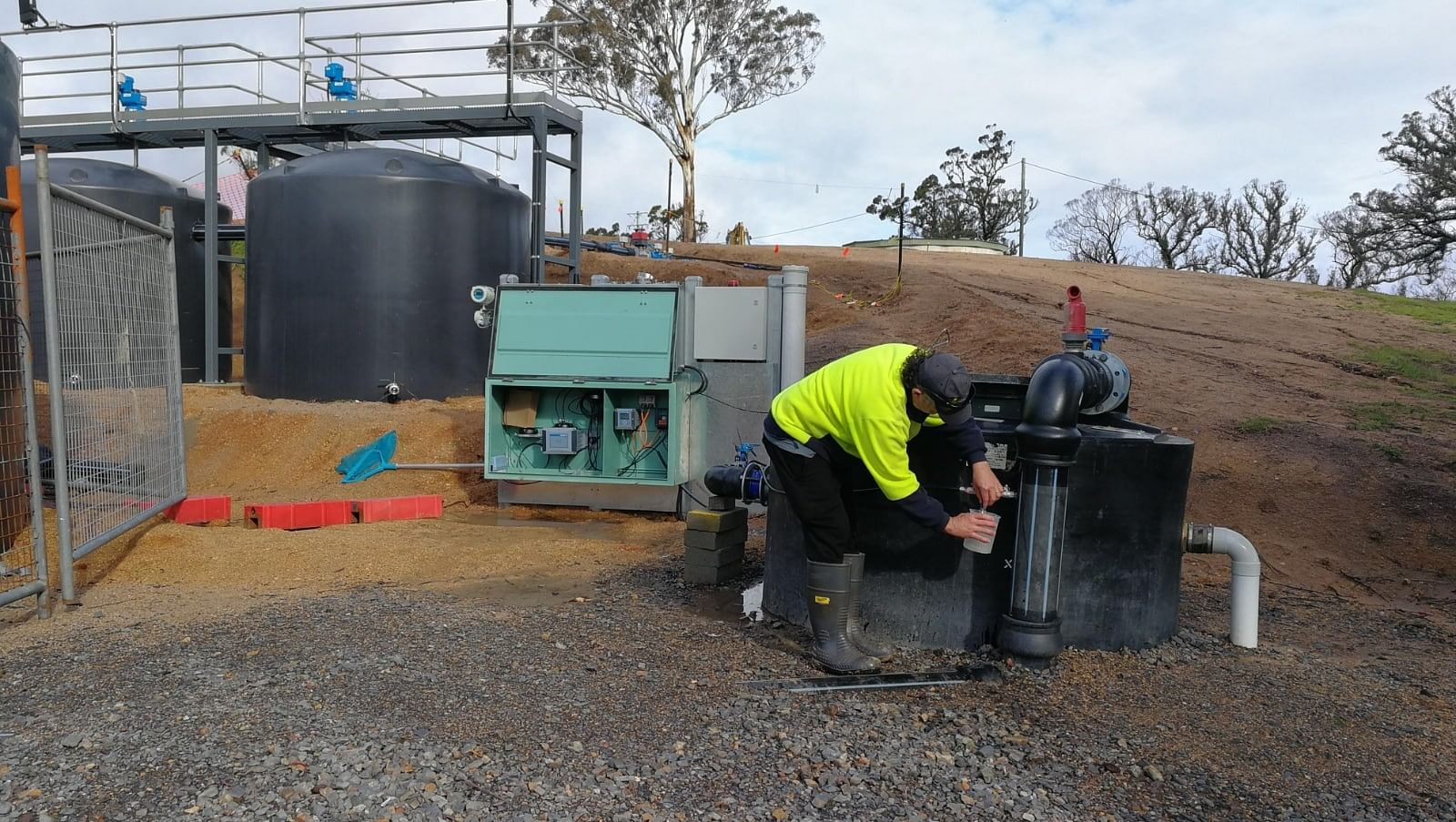 Photograph of Council's W and SS Operator, Paul Lazarro, sampling water at the temporary settling plant at Upper Brogo.