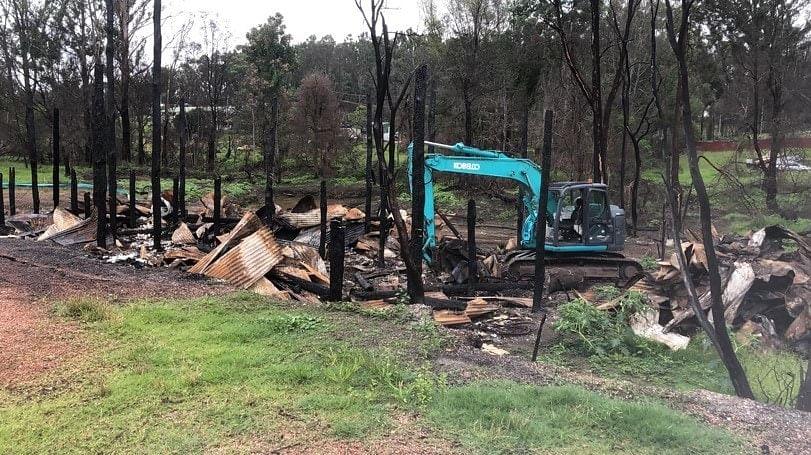 A local subcontractor cleans bushfire debris.