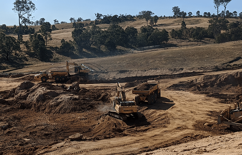 Earthmoving trucks and equipment moving soil against the backdrop of a hill studded with trees