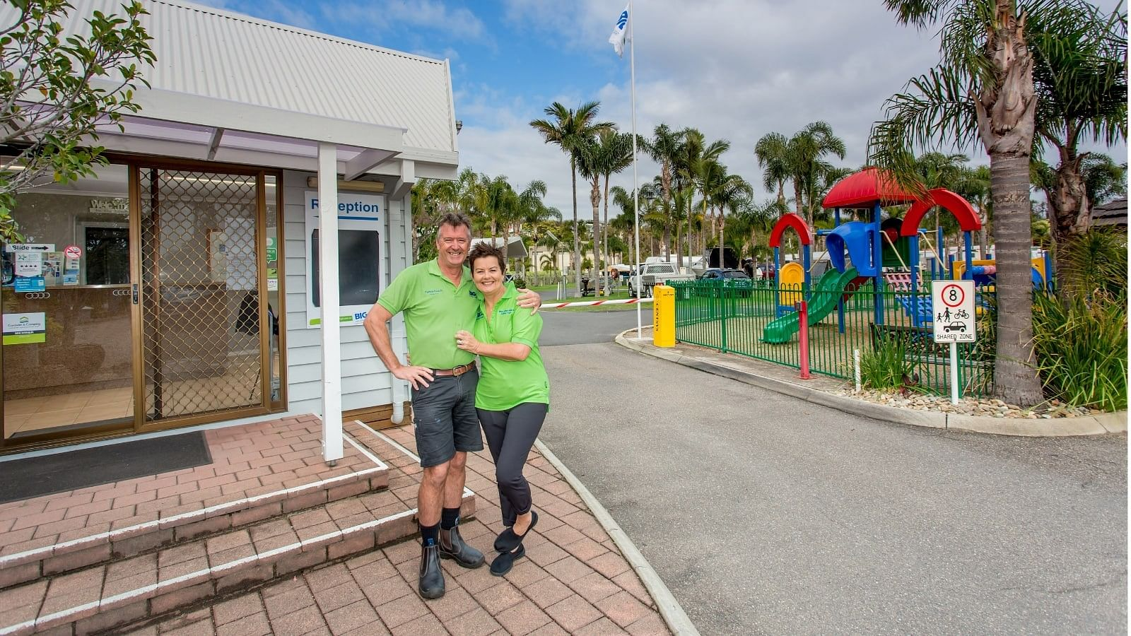 Greg and Kerry McKay standing in front of the reception building of their Big4 Tathra Beach Holiday Park.