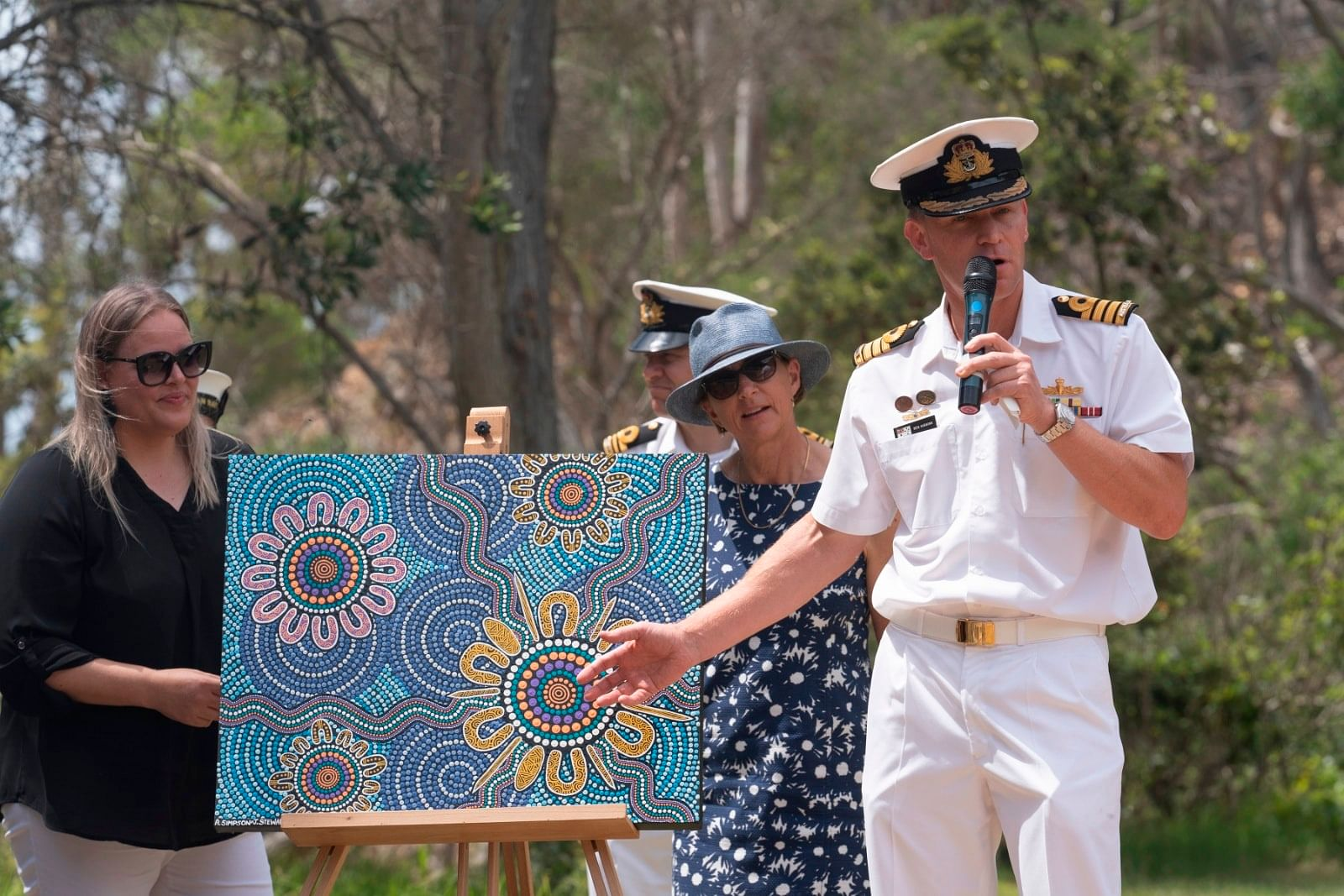 Indigenous artist Alison Simpson with the artwork that is the backdrop to the ship's mascot.