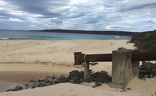 A cloudy sky over a beach showing an ocean outfall pipe in the foreground.