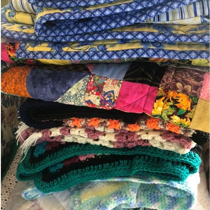 A pile of colourful hand made quilts.