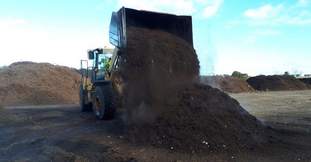 Truck dumping out compost.