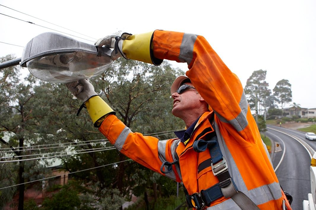 Essential energy working fixing a street light.